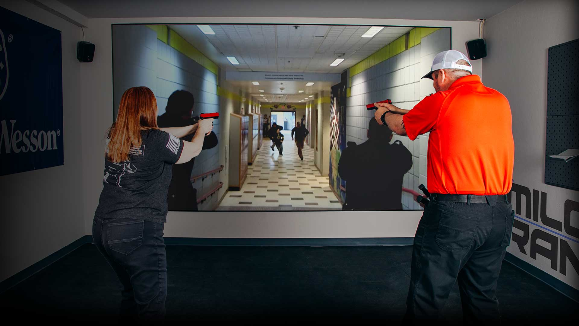 A man and a woman using our MILO virtual reality shooting range