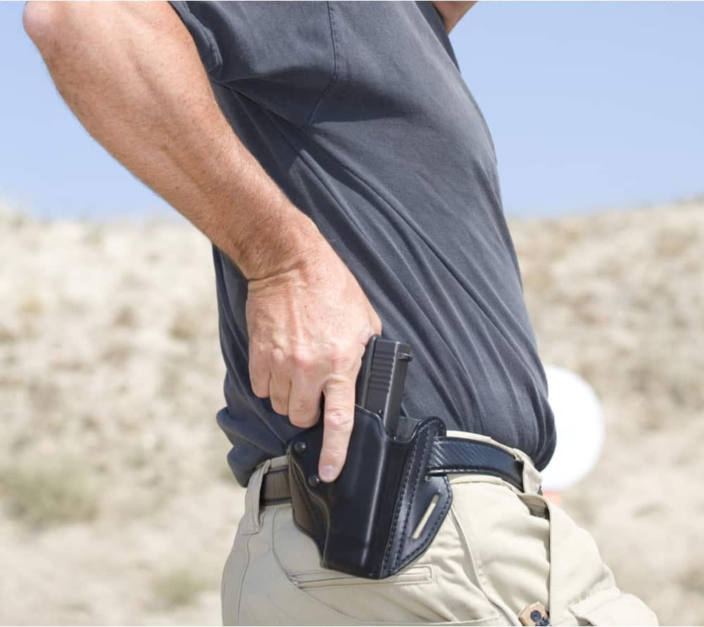 A man drawing his gun from the holster using trigger discipline