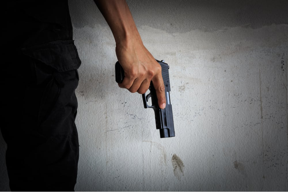 A man holding a gun with his finger resting on the frame