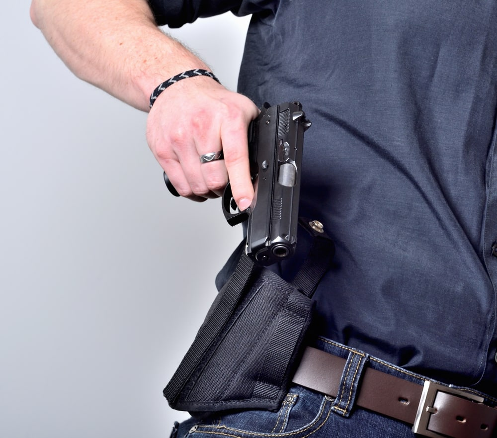 A man drawing his gun from his holster with his finger on the trigger, an example of unsafe gun handling