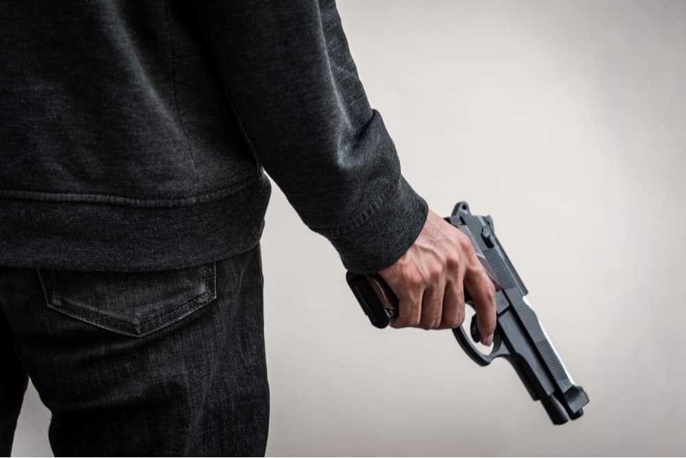 A man failing to exercise trigger discipline and holding a gun with this finger on the trigger